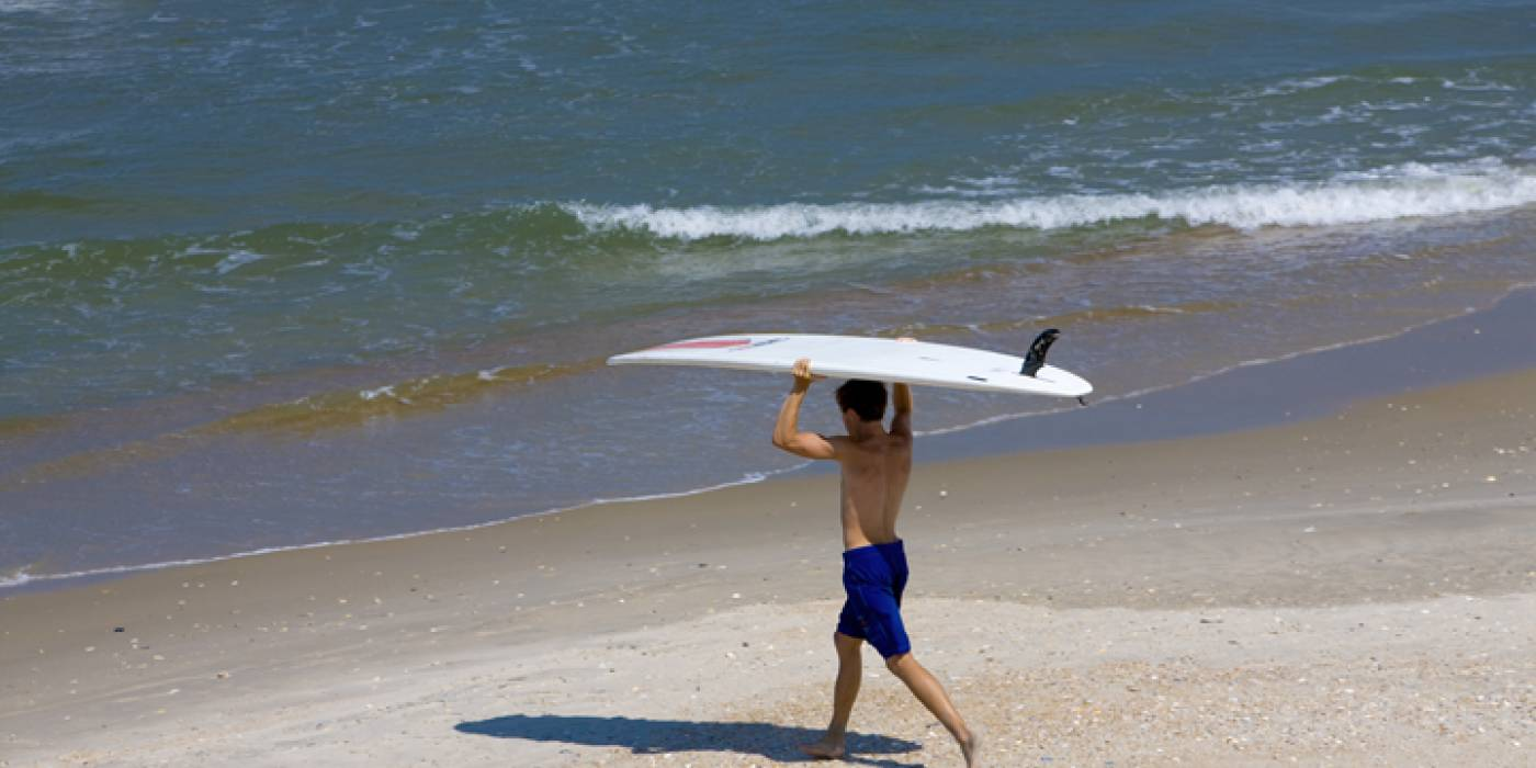 surfer heading out into ocean on beach in Corolla
